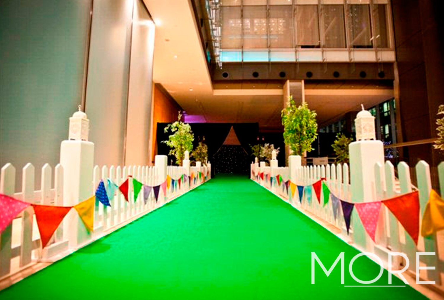 Event green carpet walkway with white picket fencing