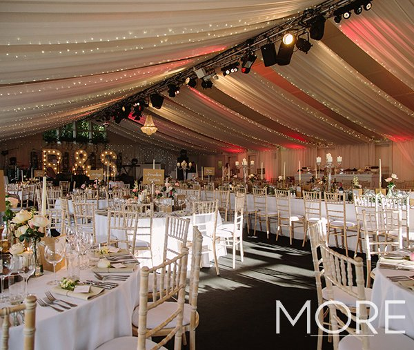 Marquee wedding decor with white linear ceiling drapes and fairy lights