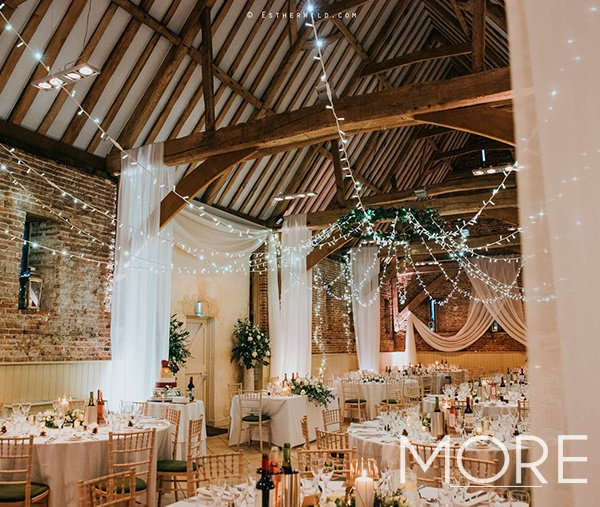 Barn wedding decor with fairy light canopy and voile drapes