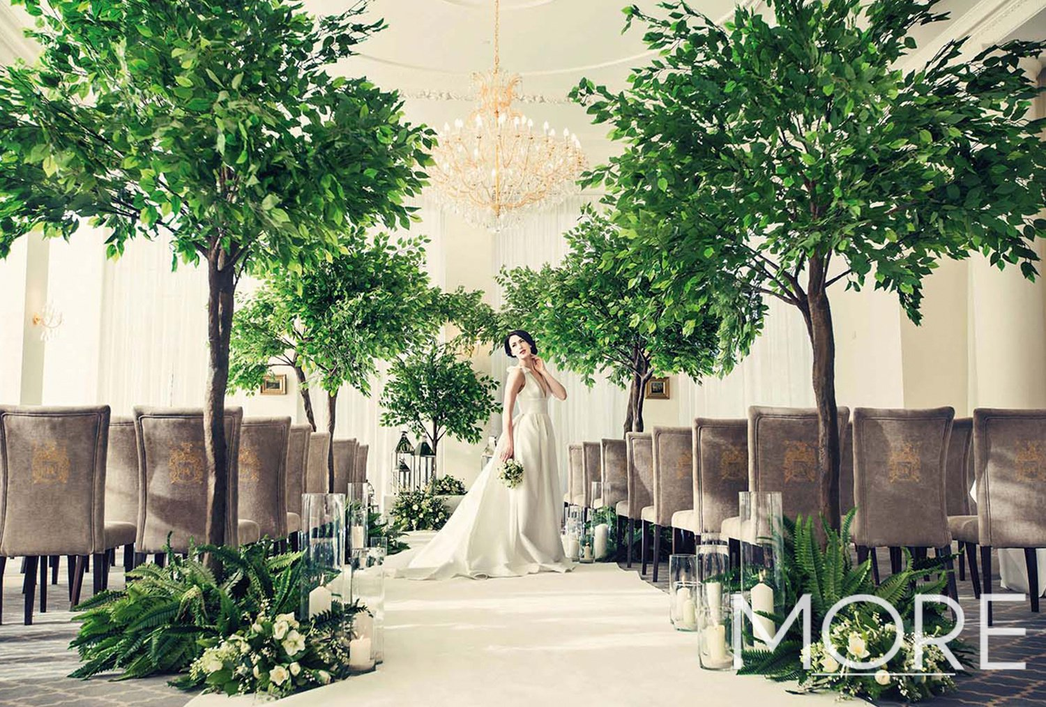 Rushton Hall wedding aisle dressing with artificial ficus trees, white carpet, glass vases and chrome lanterns