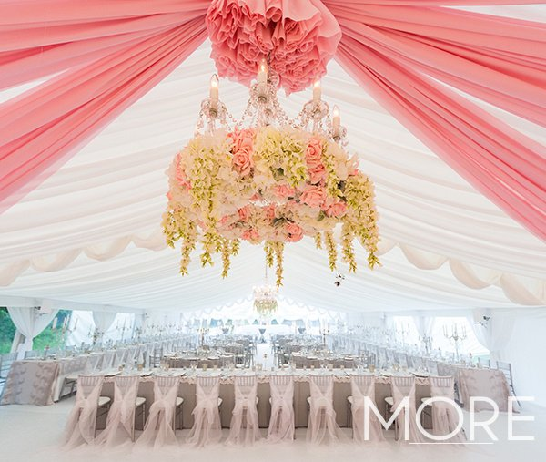 Pink radial ceiling drapes with floral chandelier marquee wedding